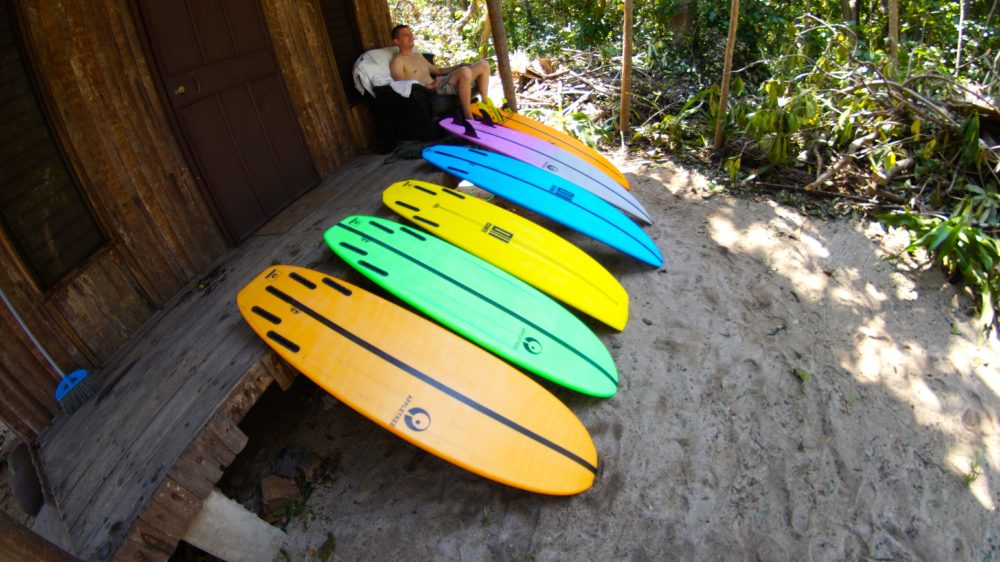 Row bright colored Appletree surfboards different shapes and sizes against wooden house