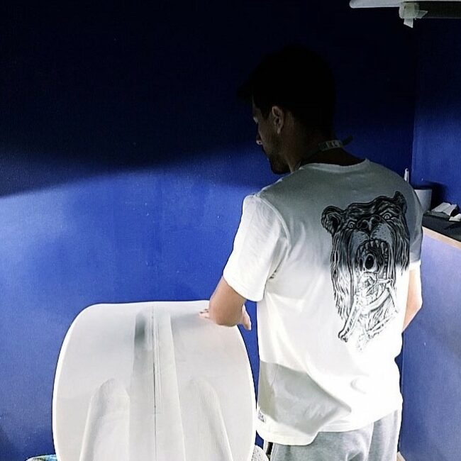 Jorge looking at blanket in blue shaping bay at the factory of Appletree Surfboards