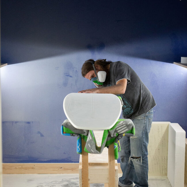 Andre shaping foam in blue shaping bay at the factory of Appletree Surfboards