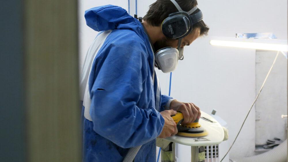Appletree crew member Joao sanding kiteboard in factory Appletree Surfboards