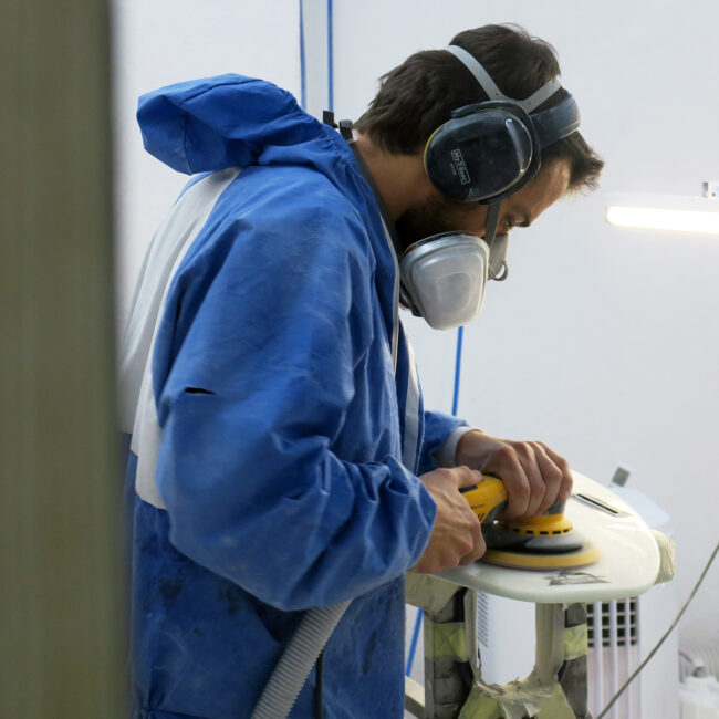 Appletree crew member Joao sanding kiteboard in factory Appletree Surfboards