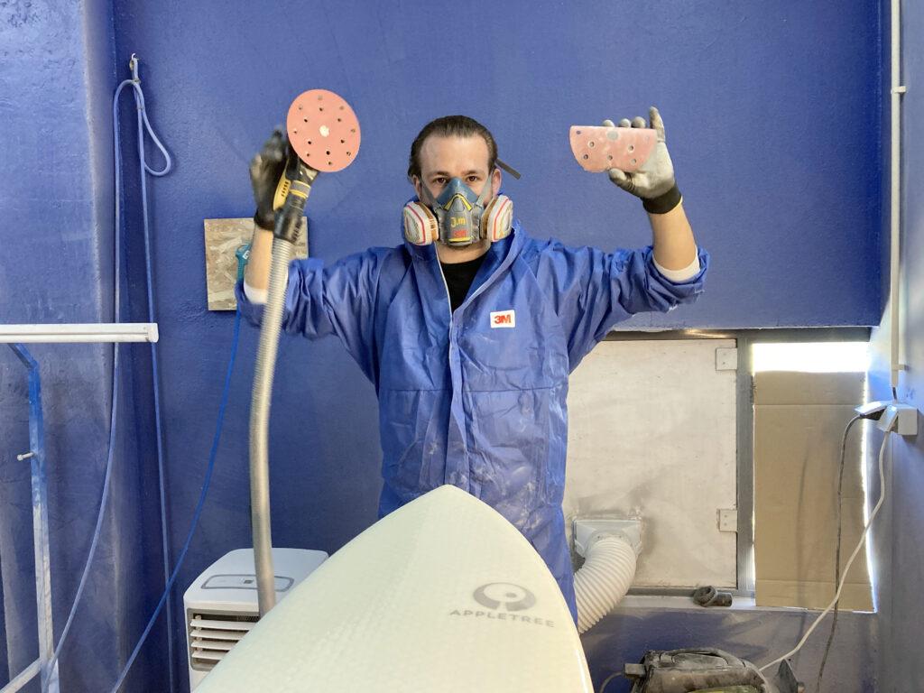 Jeroen Meere holding tools for handcrafted sanding Appletree Surfboards